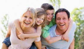 Couple giving two young children piggyback rides smiling